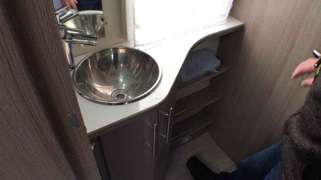 Den externe håndvask sidder i hjørnet mellem garderobeskabet, hyldeskabet og bade/toiletrummet.