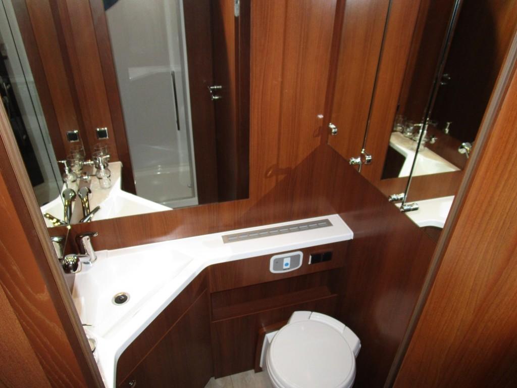 Modsat brusekabinen er toilettet. Det er et drejetoilet med god plads omkring. Rummet er med store spejle, en integreret håndvask og god plads omkring vasken. Der er godt med skabsplads og spejle på skabsdørene.