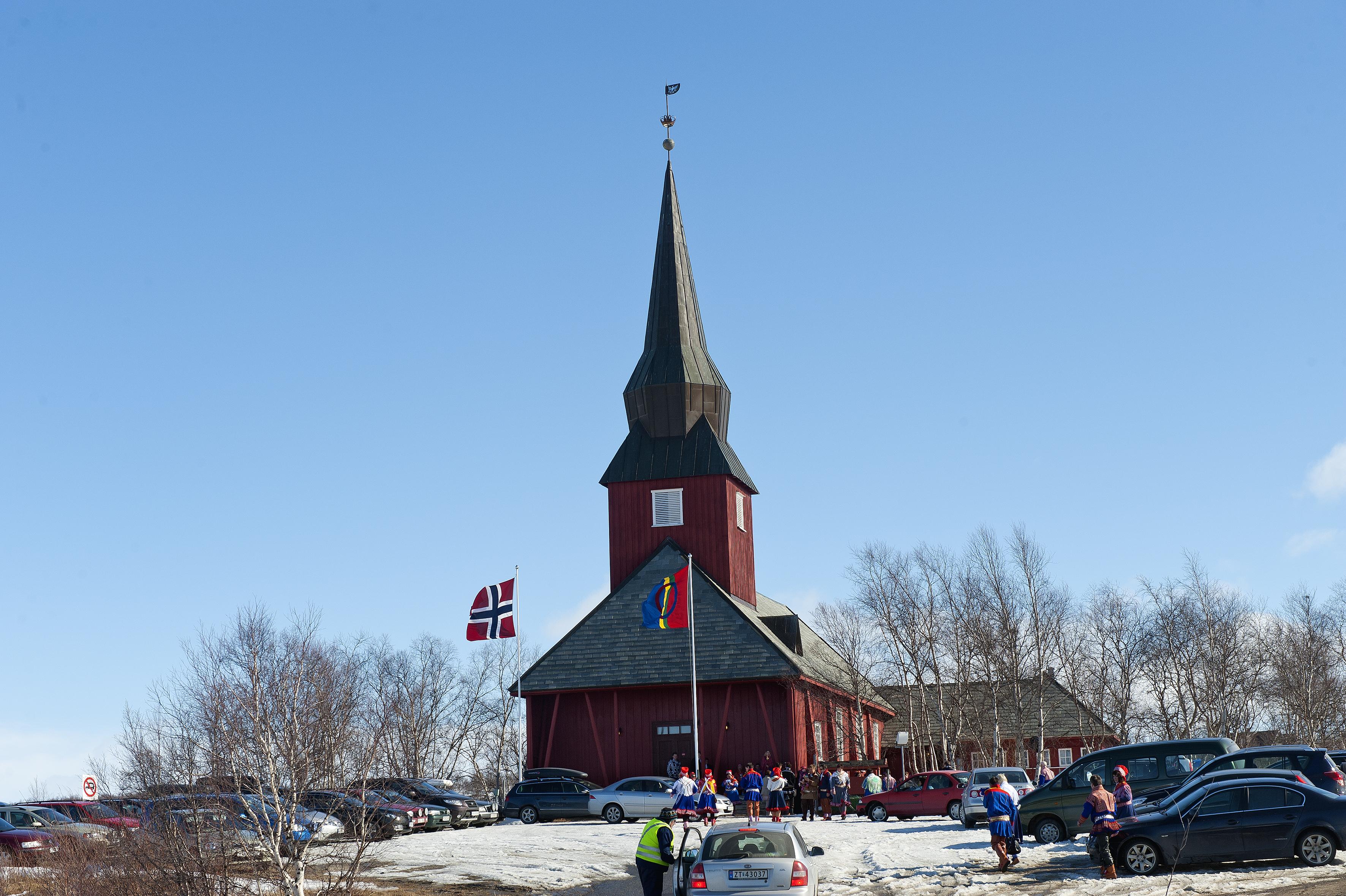 Palmelørdag er der konfirmation i Kautokeino kirke, både det norske og det samiske flag (det til højre) er hejst. Parkeringspladsen bliver fyldt af biler, og de mange mennesker er alle i de smukke samiske dragter. Der er kun et par af gæsterne der ikke har samisk dragt på.  80 – 90% kommunens indbyggere er også samer.