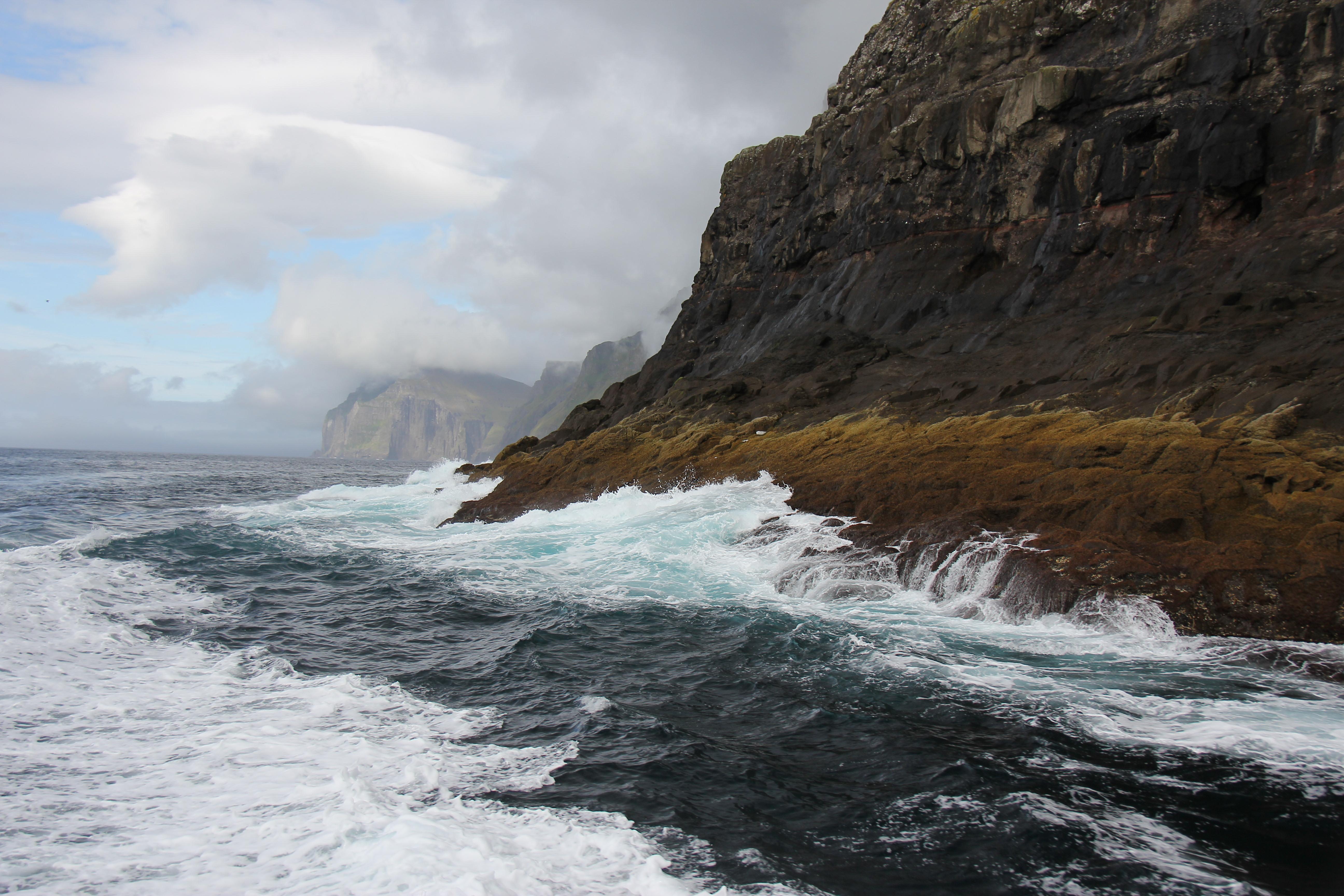 Flere steder løfter de store havdønninger os op og ned når vi sejler tæt på klipperne som kaptajnen har fortalt fortsætter flere hundrede meter direkte ned i havet.
