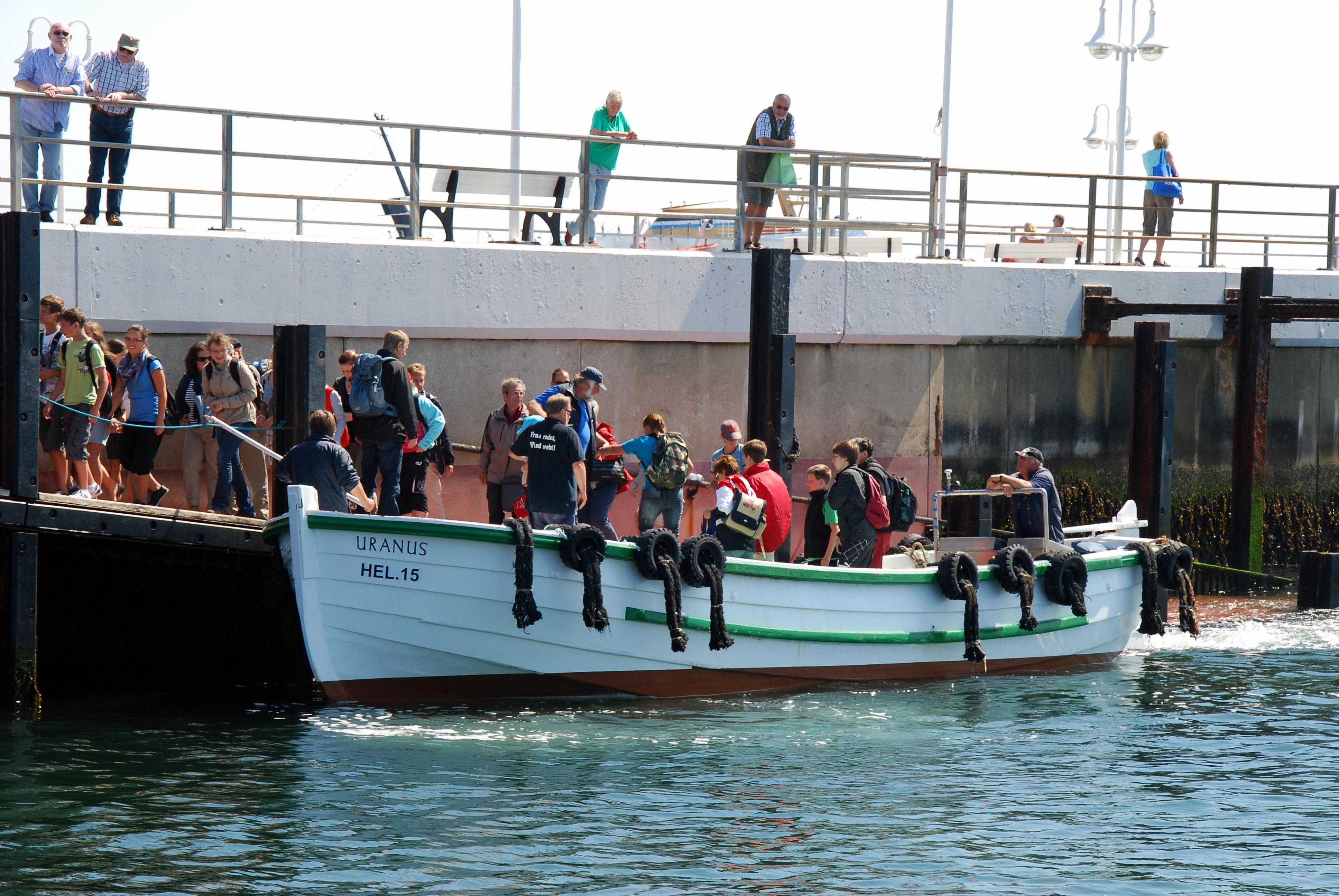 Passagerer går fra borde ved landgangsbroen der skråner ned i vandet.