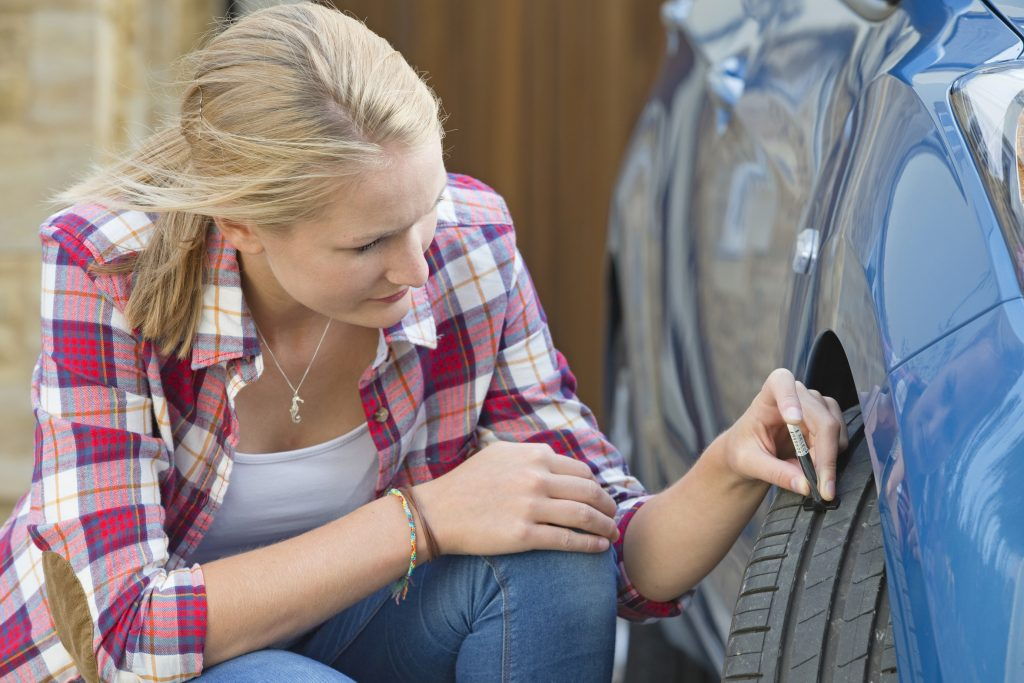 Woman Checking Tread Depth On Car Tyre